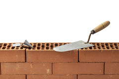 Trowel and a Plumb Bob on a Wall of Bricks. Construction tools trowel and plumb bob left on a new brickwork isolated on white Royalty Free Stock Images