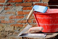 Trowel, spatula and red bucket. Trowel, spatula and bucket, bricklayer tools Royalty Free Stock Photos