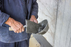 Trowel spreading mortar on concrete wall Royalty Free Stock Photo