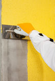 A trowel spreading a plaster on a corner-wall Royalty Free Stock Image