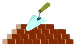 Trowel und Ziegelsteine auf Gebäude Lizenzfreie Stockbilder