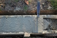 Trowel at wall foundation, concrete in formwork and tool. Concrete in wooden formwork for wall foundation with trowel tool at construction site Stock Image