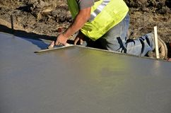 Troweling wet concrete. Construction worker troweling wet concrete on a sidewalk project Stock Photography