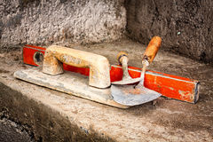 Trowels and other masonry tools on a concrete wall Stock Images