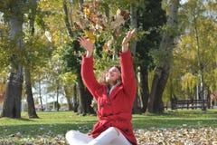 Trowing Blätter der glücklichen Herbstfrau im Park Stockfotos