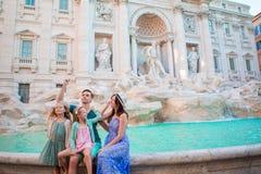 Trowing mynt för lycklig familj på Trevi-springbrunnen, Rome, för bra lycka Små flickor och föräldrar som gör en önska för att ko arkivbilder