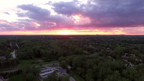 Troy Michigan Aerial. V1 Flying low backwards over neighborhood panning left with sunset views stock video footage