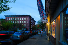 Troy NY street scene at dusk/sunset with historic buildings, traffic and activity on a Friday night. Stock Photos