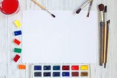 Trozo de papel, brochas y pinturas en blanco de la acuarela en pizca Imagen de archivo libre de regalías