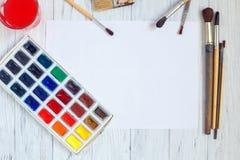 Trozo de papel, brochas y pinturas en blanco de la acuarela en pizca Fotografía de archivo libre de regalías