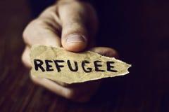 Trozo de papel con el refugiado de la palabra Fotos de archivo