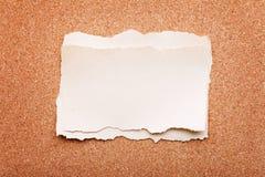 Trozo de papel rasgado en tarjeta del corcho imágenes de archivo libres de regalías