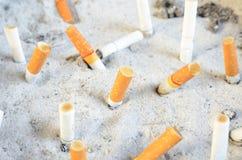 Trozo del cigarrillo en la arena Imágenes de archivo libres de regalías