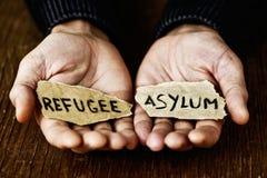 Trozos de papel con el refugiado y el asilo de las palabras Imagenes de archivo