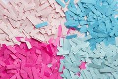 trozos de papel en colores rosados y azules Imagenes de archivo