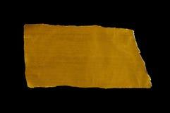 Trozos de papel rasgados oro en fondo negro Foto de archivo libre de regalías