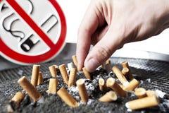 Trozos del cigarrillo en ceniza y muestra de no fumadores. Fotos de archivo libres de regalías