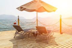 Träpir med sunbeds och slags solskydd Royaltyfri Bild