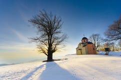Trree e chiesa ortodossa al tramonto Fotografia Stock