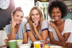 Três amigos fêmeas que apreciam o café da manhã em casa junto Fotos de Stock Royalty Free