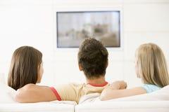 Três amigos na televisão de observação da sala de visitas Fotos de Stock Royalty Free