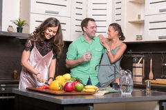 Três amigos que têm o divertimento na cozinha Fotos de Stock