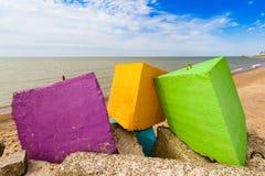 Três blocos coloridos de um quebra-mar concreto pelo mar. Foto de Stock Royalty Free