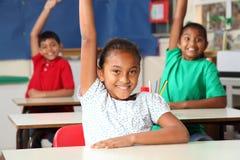 Três braços novos dos alunos levantados na classe Fotografia de Stock