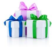 Três caixas brancas amarradas com as fitas coloridas do cetim curvam-se isolado Fotografia de Stock