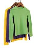 Três camisas sleeved longas em ganchos de madeira Imagens de Stock Royalty Free
