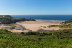 Três Cliff Bay Gower Wales Reino Unido na luz do sol do verão Imagens de Stock