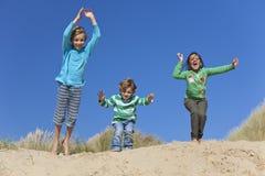 Três crianças que saltam tendo o divertimento na praia Fotografia de Stock