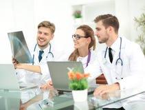 Três doutores que olham atentamente no raio X e que discutem o Foto de Stock