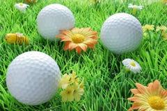 Três esferas de golfe na grama artificial Imagem de Stock Royalty Free