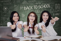 Três estudantes fêmeas que mostram os polegares acima Imagens de Stock