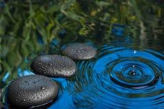 Três gotas de pedra dos termas encontram-se na água azul Imagens de Stock