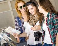 Três jovens mulheres que olham em um mapa no estação de caminhos-de-ferro ou no aeroporto europeus Recolhido em uma excursão guia Imagens de Stock Royalty Free
