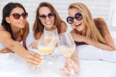 Três meninas bonitas felizes novas em beber do biquini Foto de Stock Royalty Free