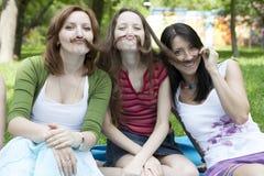 Três meninas que sentam-se na árvore Fotos de Stock Royalty Free