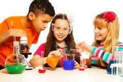 Três miúdos e laboratórios de química Fotos de Stock Royalty Free