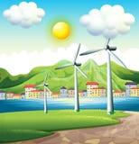 Três moinhos de vento através da vila Imagens de Stock