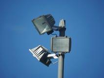 Três pentes quadrados do projetor em um polo no céu azul Fotos de Stock Royalty Free