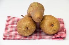Três peras em uma toalha de prato Fotografia de Stock