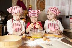 Três pouco chefsin a cozinha Imagens de Stock