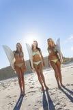 Três surfistas bonitos das mulheres nos biquinis com as prancha em Beac Fotografia de Stock Royalty Free