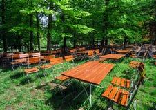 Trästolar och tabeller parkerar in kafét Arkivfoto