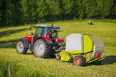 Trätor and hay-bale machinery in action Stock Photos