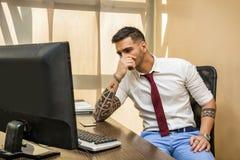 Trött eller frustrerad kontorsarbetare på datoren Arkivbilder