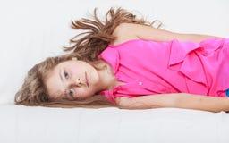 Trött utmattad lat liten flickaunge som ligger på soffan Royaltyfri Foto