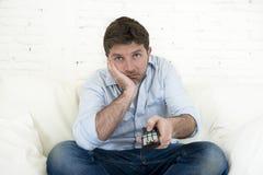 Tröttade hållande ögonen på televisionsammanträde för den uttråkade mannen på hållande fjärrkontroll för soffan att inte ha gycke Arkivfoto